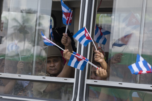 People sit in a bus heading to see the ashes of Cuba's leader Fidel Castro in Bartolome Maso, on the foothills of Sierra Maestra, Cuba, Friday, Dec. 2, 2016. Castro's ashes are on a four-day journey across Cuba from Havana to their final resting place in the eastern city of Santiago. (AP Photo/Ricardo Mazalan)